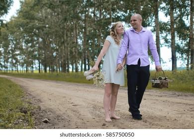 Just married lovers walking in field in autumn day