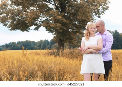 Just married lovers walking in field in autumn day