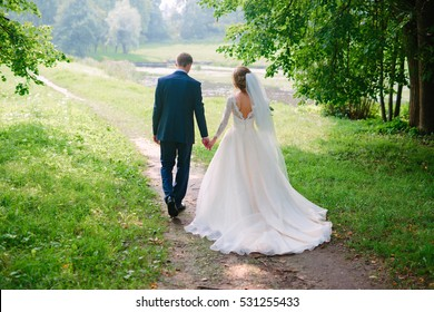Just married loving hipster couple in wedding dress and suit on a green field in the woods. happy bride and groom walking running and dancing on a summer meadow. Romantic married to a young family