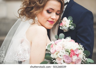 Just married wedding couple posing and bride holding in hands bouquet