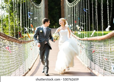 Just married, wedding couple run on bridge and look at each other