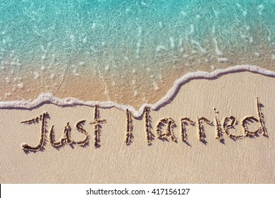 Just married written on the sand of tropical beach with soft wave of blue ocean on background