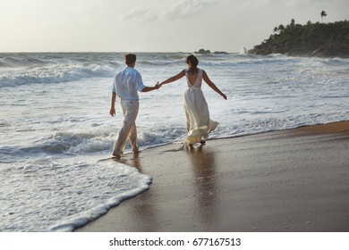 Just married young couple at the beach, enjoying the hazy dusk, wearing a wedding dress and shorts, walking barefoot, getting wet, teasing and kissing one another.