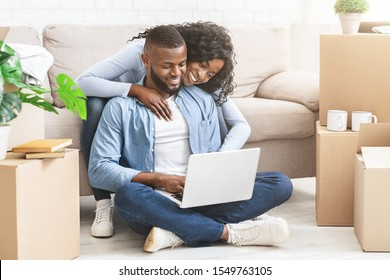 Just moved in. Black couple in love checking interior ideas for new apartment using laptop, lady hugging man from behind, copy space