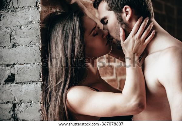 1回だけキス。れんがの壁の近くに立ってキスをする美しい若い恋人夫婦の側面