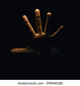 Just an open hand, and two man's eyes can be seen in the dark.