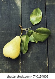 Just picked a pear on a dark wooden surface - vintage look