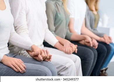 Just relax. Close up of people sitting in  row  and holding hands of each other during psychological group  therapy session