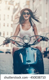 Just a road ahead. Excited young and beautiful woman riding scooter along the street and keeping mouth open