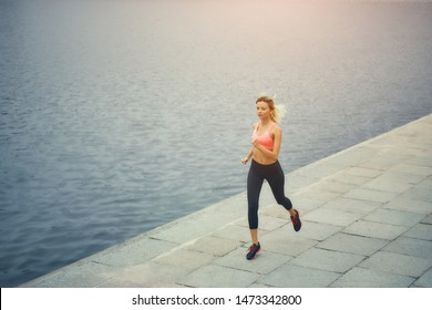 Just running. Full length of young and active blonde woman in sports clothing running along the riverbank in the morning