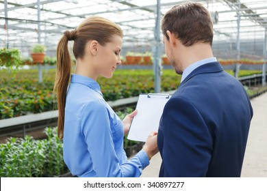 Just sign it. Pleasant businesswoman holding papers and giving it to her colleague to sign it while discussing their flower business