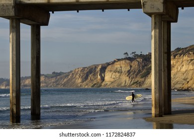 Just a surfer trying to catch some waves before the sun starts to set at Scripps pier, La Jolla CA.