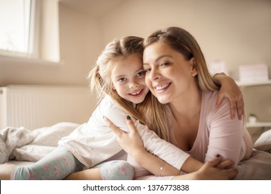 Just us girls. Mother daughter playing in bed.