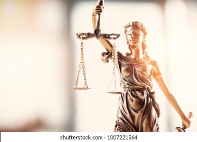 Justice blindfolded lady holding scales and sword statue