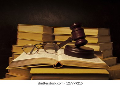 Justice gavel and eye glasses on pile of law books