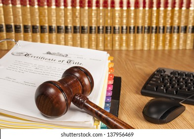 Justice gavel on certificate of title with legal books and computer keyboard in the background