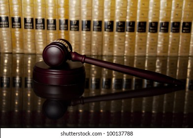 Justice gavel with reflection on glass table with law books in the background