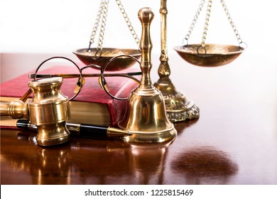 Justice gavel, scales, bell, round-rimmed glasses, a book and pen on the table