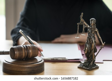 justice and law concept. Female judge in a courtroom on wooden table and Counselor or Male lawyer working in office. Legal law, advice and justice concept.