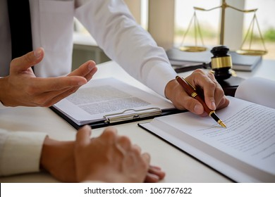 Justice and Law concept. Legal counsel presents to the client a signed contract with gavel and legal law or legal having team meeting at law firm in background