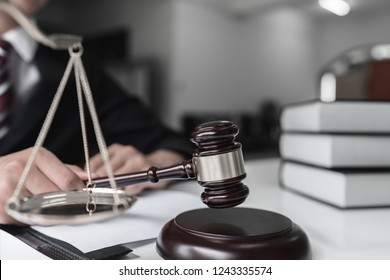 Justice and law concept. Male judge in a courtroom striking the gavel on wood table