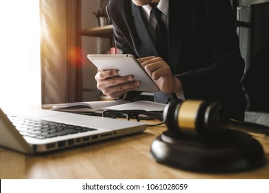 justice and law concept.Male judge in a courtroom  the gavel,working with digital tablet computer on wood table in morning light