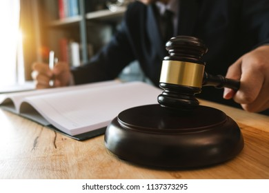 Justice and law concept.Male judge in a courtroom with the gavel,working with,digital tablet computer docking keyboard,eyeglasses,on wood table