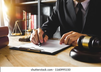 justice and law concept.Male judge in a courtroom  the gavel, working with digital tablet computer on wood table in morning light