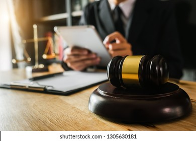 justice and law concept.Male judge in a courtroom  the gavel, working with smart phone and laptop and digital tablet computer on wood table in morning light