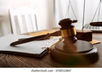 Justice and law concept.Male judge in a courtroom with the gavel, working with, computer and docking keyboard, eyeglasses, on table in morning light