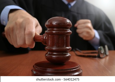 justice and law concept.Male judge in a courtroom striking the gavel,working with digital tablet computer docking keyboard on wood table