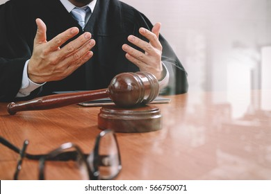 justice and law concept.Male judge in a courtroom with the gavel,working with smart phone,digital tablet computer docking keyboard,eyeglasses,on wood table,filter effect