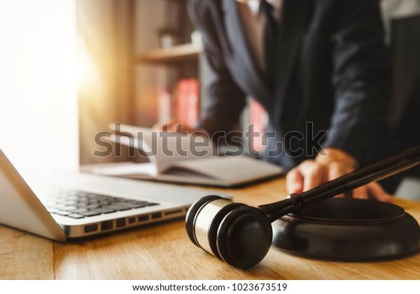Recht und Recht Konzept.Männliche Richter in einem Gerichtssaal der Spielwagen, mit digitalem Tablet-Computer auf Holztisch in Morgenlicht