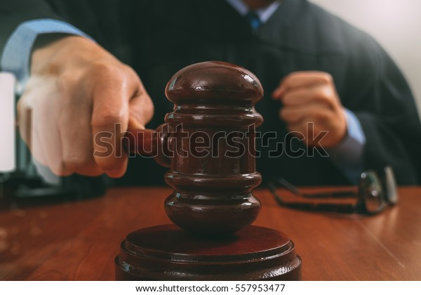 justice and law concept.Male judge in a courtroom striking the gavel,working with digital tablet computer docking keyboard on wood table,filter effect