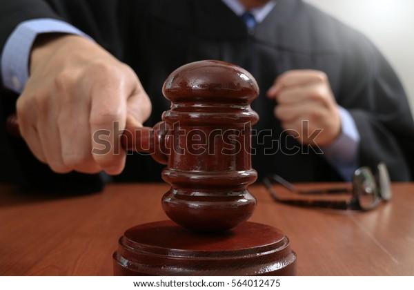 Recht und Recht Konzept.Männer Richter in einem Gerichtssaal, der auf den Handschuh fällt, arbeiten mit digitalen Tablet-Computer-Docking-Tastatur auf Holztisch