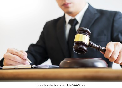 justice and law concept.Male judge lawyer in a courtroom giving verdict by hitting mallet gavel on sounding block with documents
