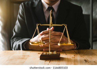 justice and law concept.Male lawyer in the office with brass scale on wooden table in morning light