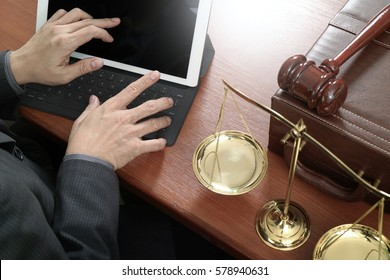 justice and law concept.Male lawyer in office with the gavel,working with smart phone,digital tablet computer docking keyboard,brass scale,on wood table