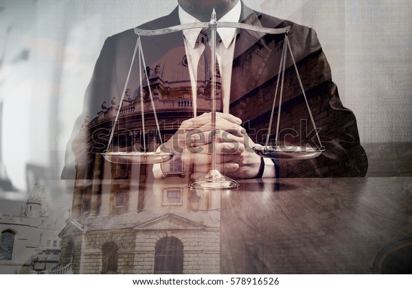 justice and law concept.Male lawyer in the office with brass scale on wooden table with london city background,double exposure