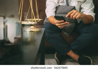 Justice and Law context.Male lawyer hand sitting on sofa and working with smart phone,digital tablet computer docking keyboard with gavel and document on living table at home,filter effect
