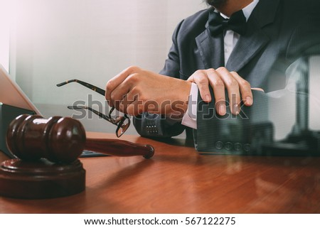 Justice and Law context.Male lawyer hand working with smart phone,digital tablet computer docking keyboard with gavel and document on wood table,filter effect