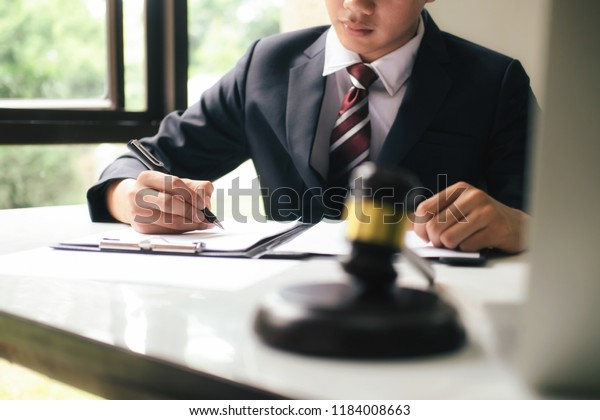 Justice and lawfirm concept.Male lawyer in the office with brass scale.