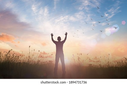 Justice and restorative concept: Silhouette of healthy man raised hands at meadow sunset background