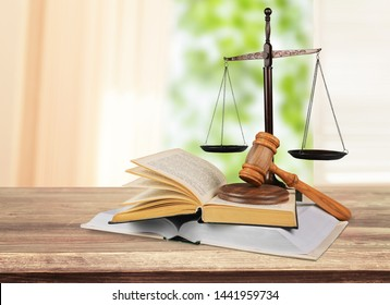 Justice scale and wooden gavel on open book