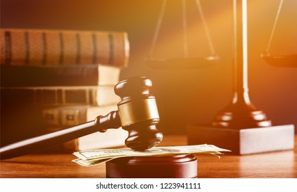 Justice Scales and books and wooden gavel with money on table. Justice concept