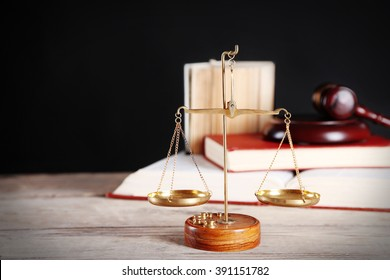 Justice scales with wooden gavel and books on black background