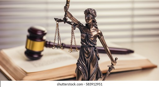 justice Statue with gavel on a open law book