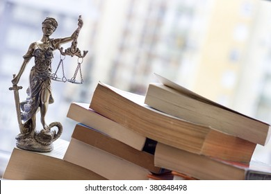 Justice statue with sword and scale and books. Law concept