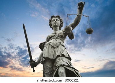 justice statue with sword and scale. cloudy sky in the background.