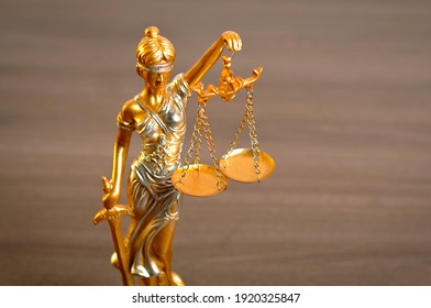 Justice woman statue sculpture isolated on brown wood background law lawyer symbol antique vintage classic metal golden gold yellow judge